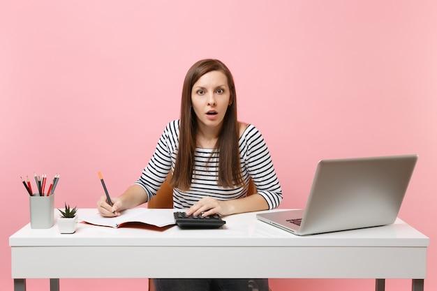 Donna scioccata che usa la calcolatrice scrivendo note con calcoli si siede e lavora in ufficio con un laptop pc contemporaneo isolato su sfondo rosa pastello. concetto di carriera aziendale di successo. copia spazio.