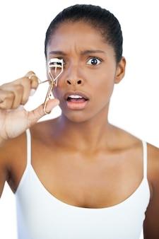 Donna scossa usando il bigodino per le sue ciglia