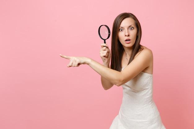 Donna scioccata in abito bianco che punta il dito indice da parte e tiene la lente d'ingrandimento