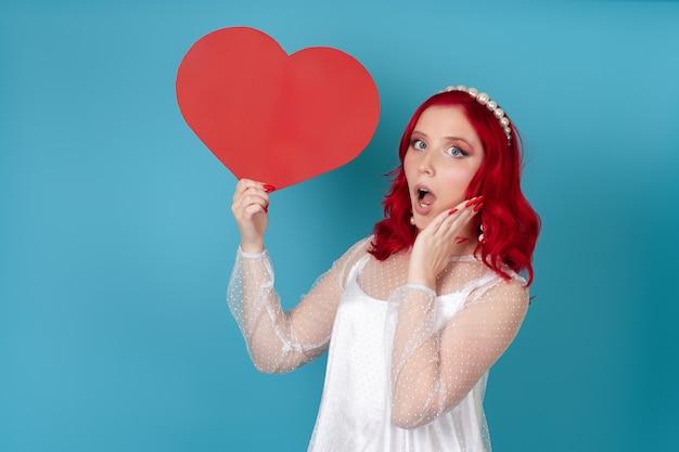 Donna scioccata con la bocca aperta in abito bianco e capelli rossi che tiene un grande cuore di carta rossa