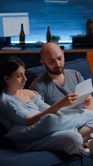 Scioccato preoccupato frustrato confuso giovane coppia disperata che legge avviso di sfratto in scartoffie lett...