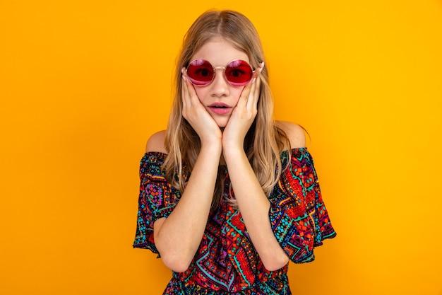 Giovane donna slava bionda scioccata con occhiali da sole che si mette le mani sul viso e guarda