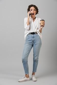 Donna giovane scioccata di affari che posa isolata sopra il muro grigio che parla dal caffè bevente del telefono cellulare