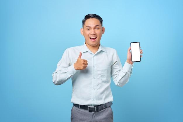 Giovane uomo d'affari scioccato che mostra lo schermo vuoto dello smartphone e fa i pollici in su su sfondo blu