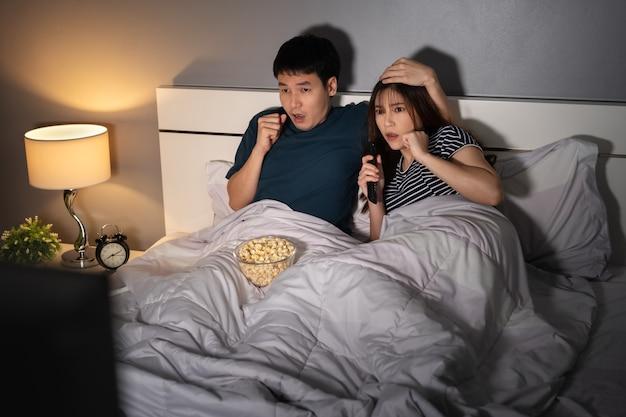 Una giovane coppia scioccata che guarda un film in tv di notte sul letto