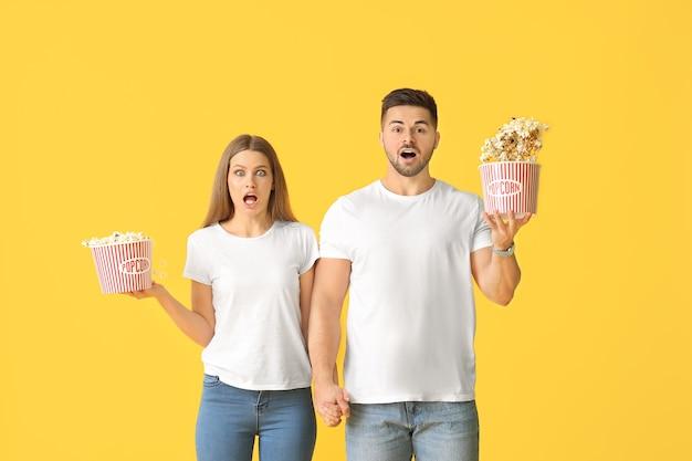 Giovani coppie scioccate con popcorn su sfondo colorato