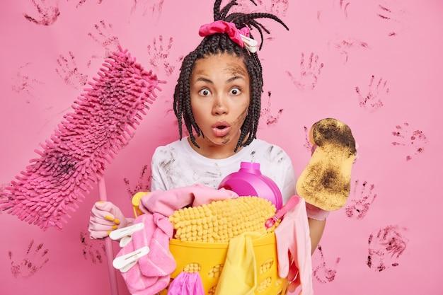 La giovane cameriera etnica scioccata guarda la stanza molto sporca con il caos intorno tiene spugna e scopa impegnata a riordinare la cucina raccoglie la biancheria nel cesto fa le faccende domestiche posa contro il muro rosa