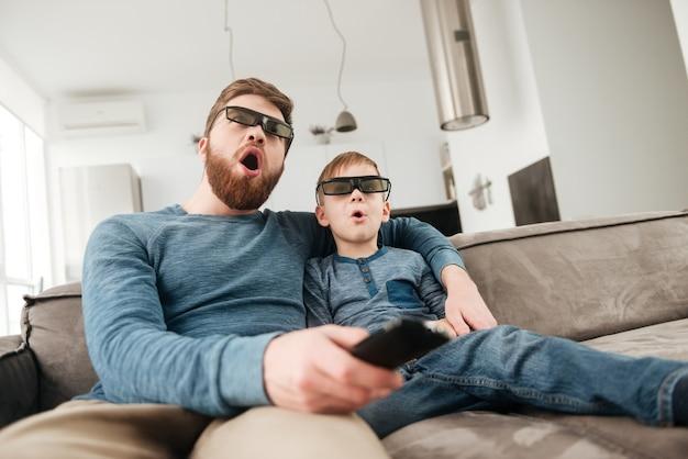 Scioccato giovane padre che tiene il telecomando mentre guarda la tv con il suo piccolo figlio carino usando occhiali 3d.