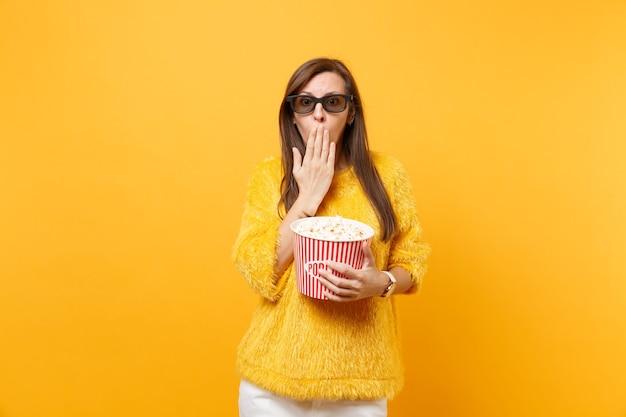 Ragazza scioccata in occhiali imax 3d che copre la bocca con la palma che guarda film che tiene in mano un secchio di popcorn isolato su sfondo giallo brillante. persone sincere emozioni nel cinema, concetto di stile di vita.
