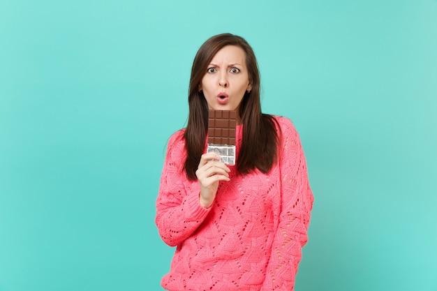 Scioccato giovane ragazza in maglia maglione rosa tenere in mano barretta di cioccolato tenendo la bocca spalancata isolato su sfondo blu muro turchese, ritratto in studio. concetto di stile di vita della gente. mock up copia spazio.