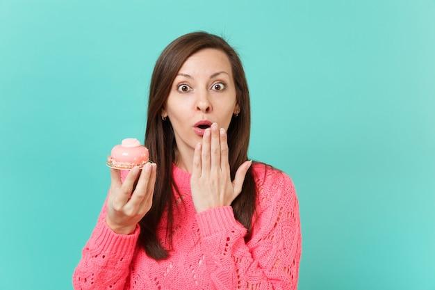 Giovane ragazza scioccata in maglione rosa lavorato a maglia che tiene la bocca spalancata coprendo la bocca con la palma tenere in mano la torta isolata su sfondo blu ritratto in studio. concetto di stile di vita della gente. mock up copia spazio.