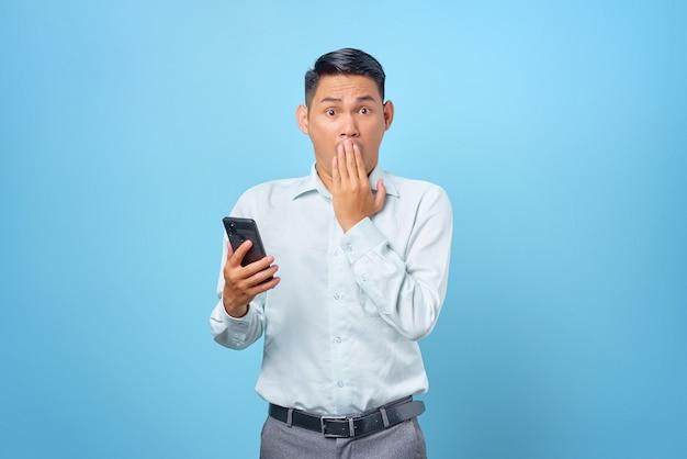 Scioccato giovane uomo d'affari bello che tiene smartphone e copre la bocca su sfondo blu