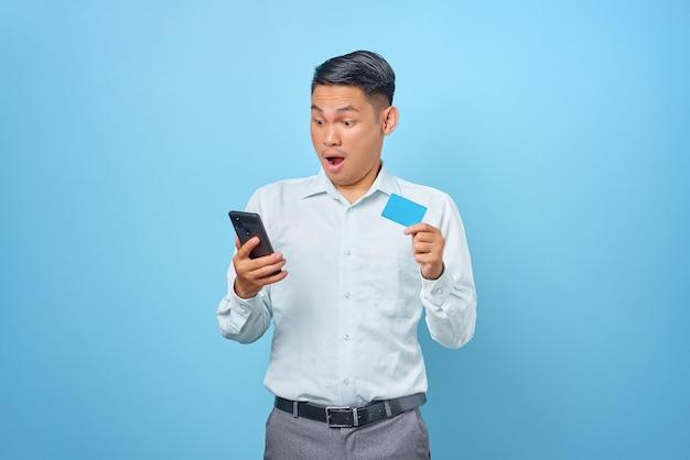 Scioccato giovane uomo d'affari bello che tiene smartphone e carta di credito su sfondo blu