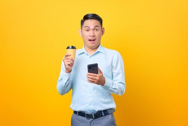 Scioccato giovane uomo d'affari bello che tiene smartphone e tazza di caffè su sfondo giallo