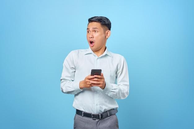 Scioccato giovane uomo d'affari bello che tiene smartphone e guarda da parte su sfondo blu