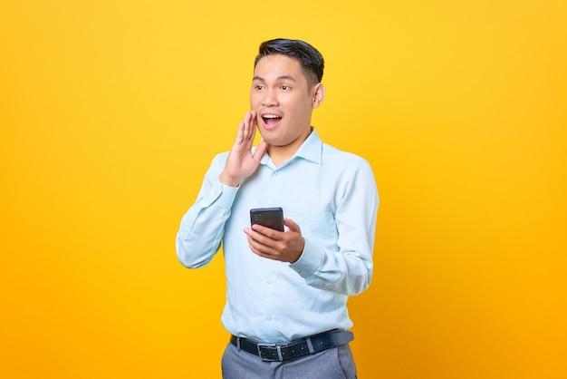 Scioccato giovane uomo d'affari bello che tiene smartphone e guarda da parte su sfondo giallo