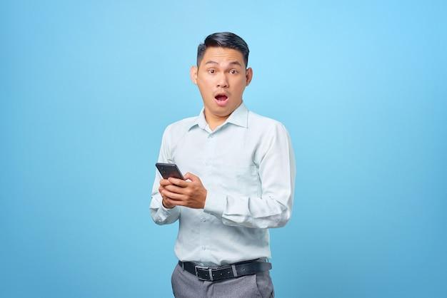 Scioccato giovane uomo d'affari bello che tiene smartphone e guarda la telecamera su sfondo blu