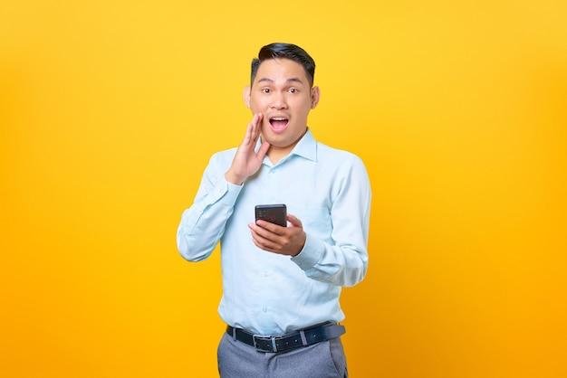 Scioccato giovane uomo d'affari bello che tiene smartphone e guarda la macchina fotografica su sfondo giallo