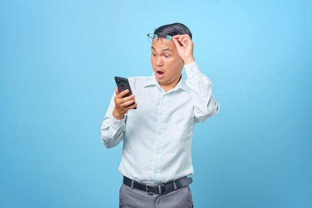 Scioccato giovane uomo d'affari bello che utilizza smartphone e si toglie gli occhiali su sfondo blu