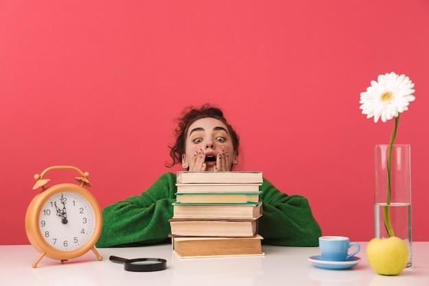 Ragazza giovane studentessa scioccata che tiene le sue guance e guardando i libri mentre era seduto al tavolo