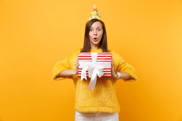 Scioccato giovane donna in cappello di compleanno che tiene scatola rossa con regalo presente celebrando, godendo la vacanza isolato su sfondo giallo brillante. persone sincere emozioni, concetto di stile di vita. zona pubblicità.