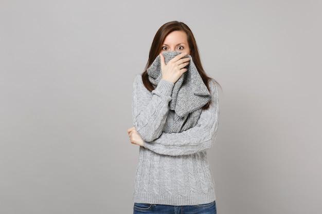 Scioccato giovane donna in maglione grigio che copre la bocca con sciarpa isolato su sfondo grigio ritratto in studio. stile di vita sano, persone sincere emozioni, concetto di stagione fredda. mock up copia spazio.