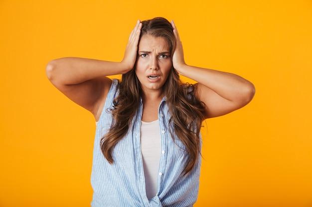 Giovane donna scioccata, tenendo le braccia alla testa
