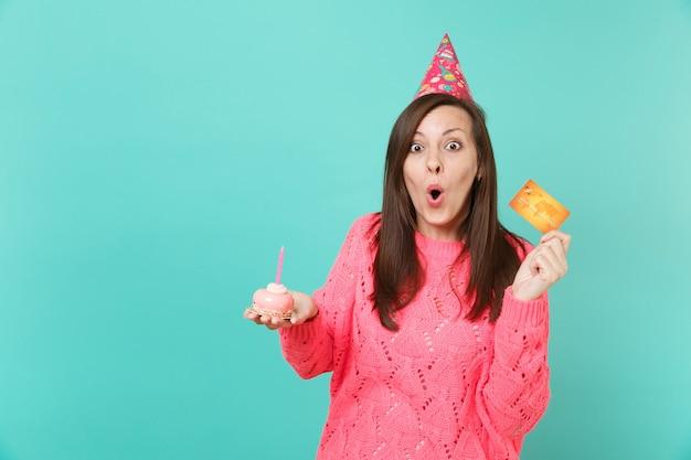 Giovane donna scioccata in maglione rosa lavorato a maglia, cappello di compleanno che tiene la bocca spalancata, tenere in mano la torta con carta di credito candela isolata su sfondo blu. concetto di stile di vita della gente. mock up copia spazio.