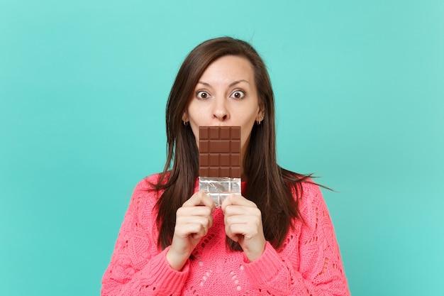 Scioccato giovane donna in maglia maglione rosa tenere in mano, coprendo la bocca con barretta di cioccolato isolato su sfondo blu muro turchese, ritratto in studio. concetto di stile di vita della gente. mock up copia spazio.