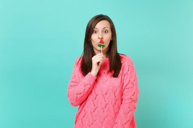 Giovane donna scioccata in maglione rosa lavorato a maglia che tiene in mano, coprendo la bocca con lecca-lecca cocomero isolato su sfondo blu muro, ritratto in studio. concetto di stile di vita della gente. mock up copia spazio.