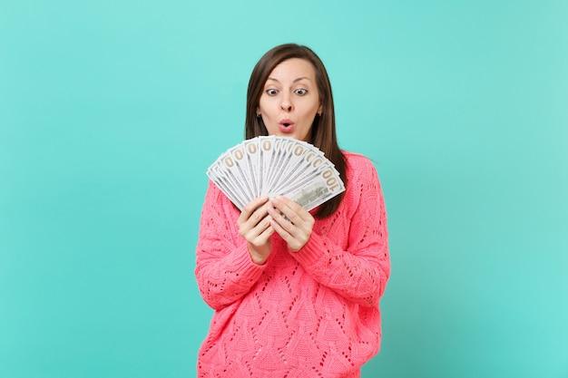 Giovane donna scioccata in maglione rosa lavorato a maglia che guarda un sacco di banconote in dollari, denaro contante in mani isolate su sfondo blu muro in studio. concetto di stile di vita della gente. mock up copia spazio.