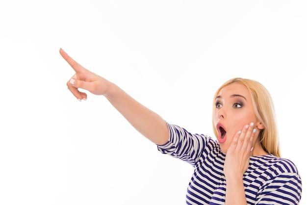 Giovane donna scioccata che punta lontano e tocca il viso
