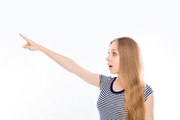 Giovane donna scioccata che punta lontano su uno spazio bianco