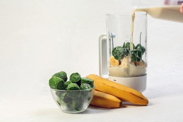 Spinaci surgelati banana e latte d'avena per un frullato sano concetto di alimentazione sana