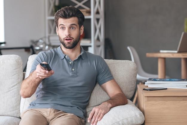 Programma televisivo scioccante. bel giovane che tiene il telecomando e sembra sorpreso mentre guarda la tv sul divano di casa