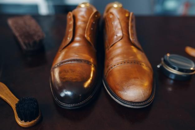 Concetto di servizio di riparazione di scarpe, primo piano riparato degli stivali, posto di lavoro del calzolaio, nessuno laboratorio di calzoleria, calzature riparate sul tavolo, lavoro di calzolaio
