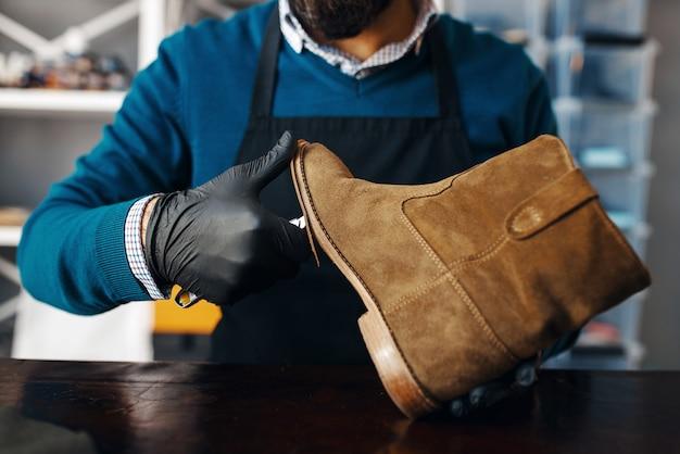 Il calzolaio ripara la scarpa, servizio di riparazione delle calzature