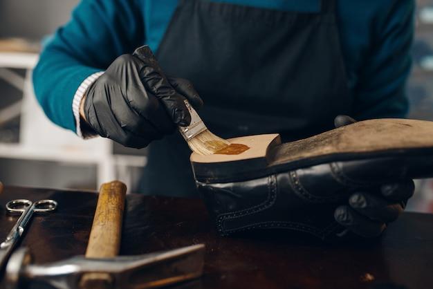 Il calzolaio spalma la colla sulla scarpa, servizio di riparazione di calzature.