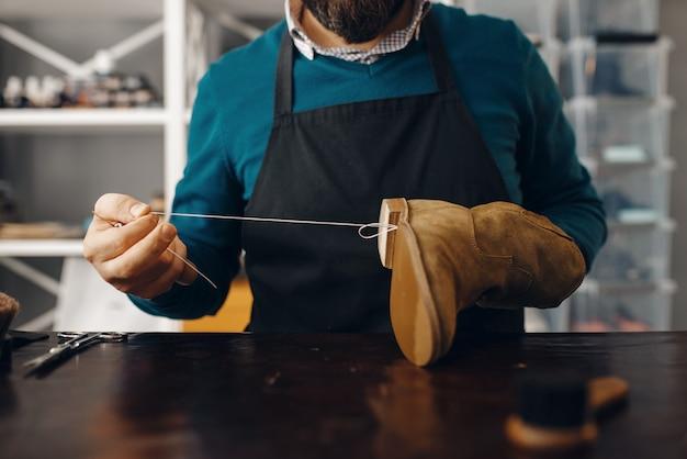 Il calzolaio cuce la scarpa, servizio di riparazione di calzature