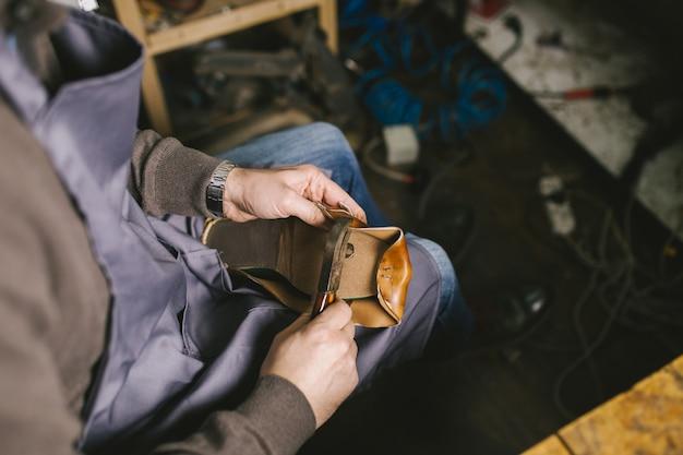 Calzolaio in officina che fa scarpe di cuoio.
