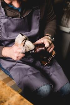 Calzolaio in officina che lucida nuove belle scarpe di cuoio fatte a mano.