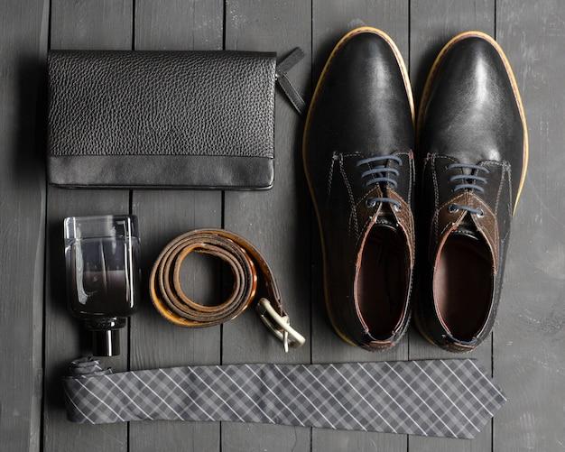 Scarpe e accessori per uomo giacciono sul pavimento di legno