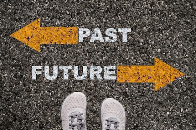 Scarpe su strada asfaltata con freccia gialla opposta e concetto di formulazione futuro passato.