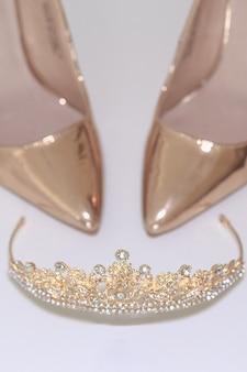 A scarpe e corona su uno sfondo bianco. il concetto di una festa di matrimonio, damigella d'onore e addio al nubilato.