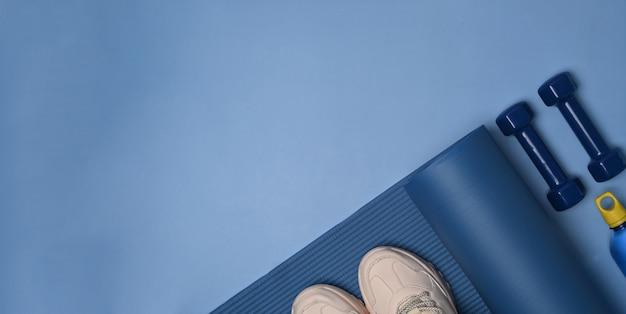 Scarpe, smartphone, bottiglia d'acqua, tappetino e manubri su sfondo blu.