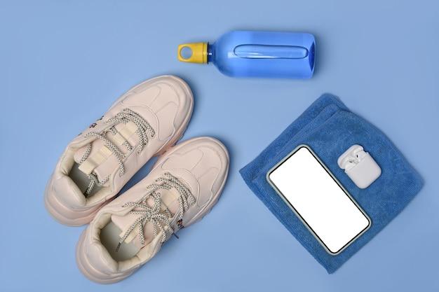 Scarpe, smartphone, auricolare e bottiglia d'acqua su sfondo blu.