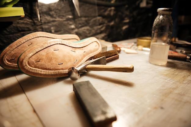 Scarpe sul tavolo presso l'officina calzaturiera.