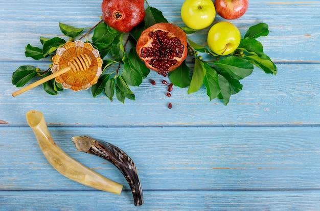Shofar e miele con la mela sulla tavola di legno blu.