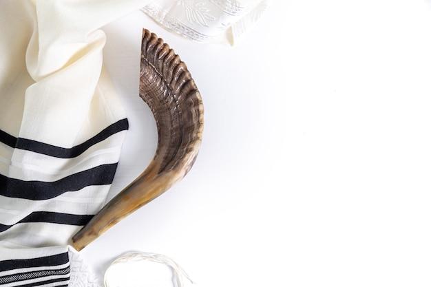 Shofar (corno) e tallit su sfondo bianco. simbolo tradizionale della festa ebraica. vista dall'alto