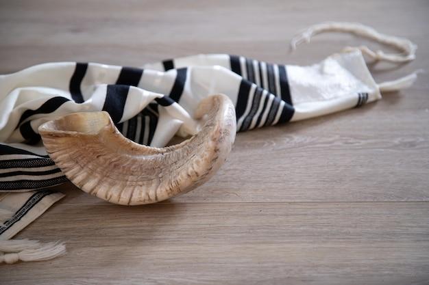 Shofar (corno) e tallit su uno sfondo di legno. simbolo tradizionale della festa ebraica.